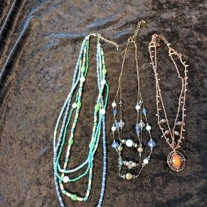 Three necklaces.  Blues, greens and rust.